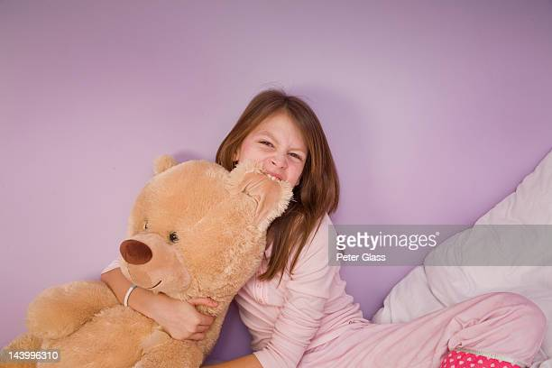 Preteen girl with her large teddy bear.