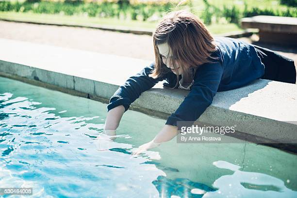 Preteen girl with short hair dipping hands in fountain water