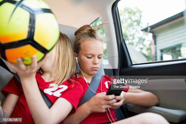 pre-teen girls in backseat of car - kids inside car stock photos and pictures