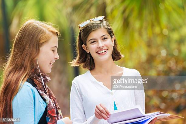 Preteen girls looking at school book assignment together after class