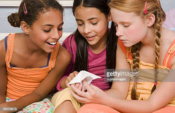 Pre-teen girls playing fortune telling game