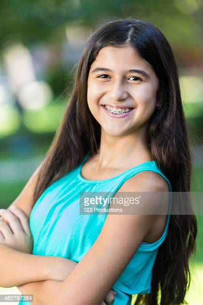 preteen hispanic girl with braces smiling outdoors - beautiful girl smile braces vertical stock photos and pictures