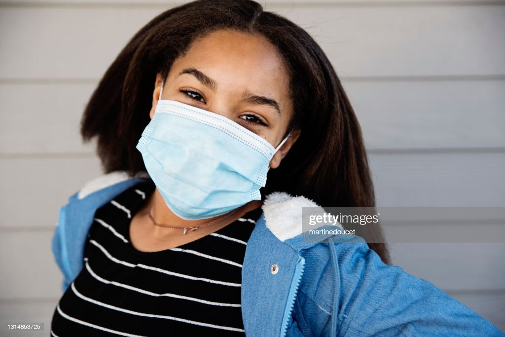 Preteen mixed-race girl smiling behind protective mask outdoors. : Stock Photo