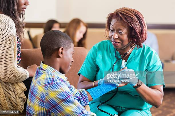 Preteen patient being examined by nurse in hospital waiting area