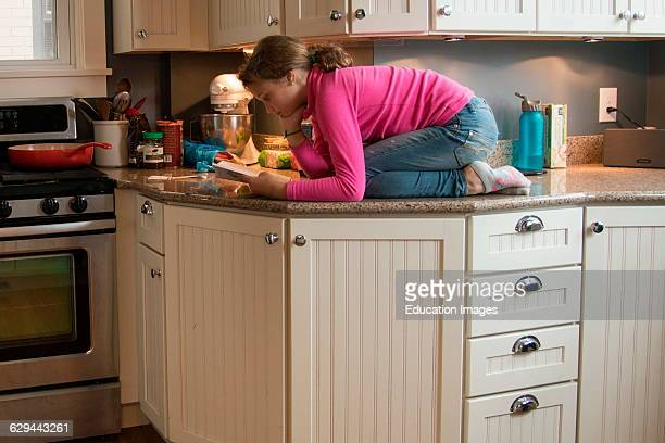 Preteen reads book on counter top