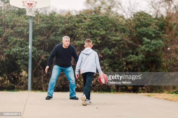 pre-teen son and father playing basketball on playground