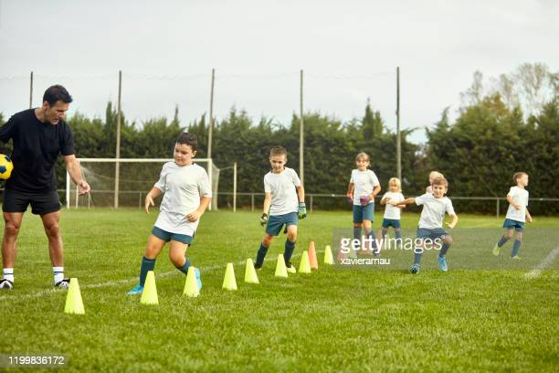 preteen spanish footballers doing agility drills with coach - sports training drill stock pictures, royalty-free photos & images