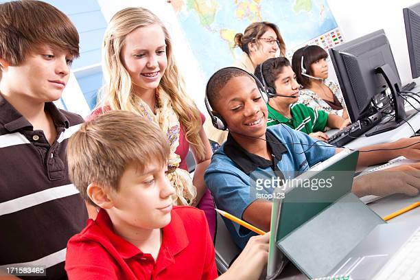 Pre-teen students in computer lab with instructor. Classroom, school, education.