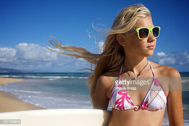 A pre-teen surfer girl wearing sunglasses poses for the camera at Paia Beach, Maui, Hawaii as her hair is being blown by the wind.