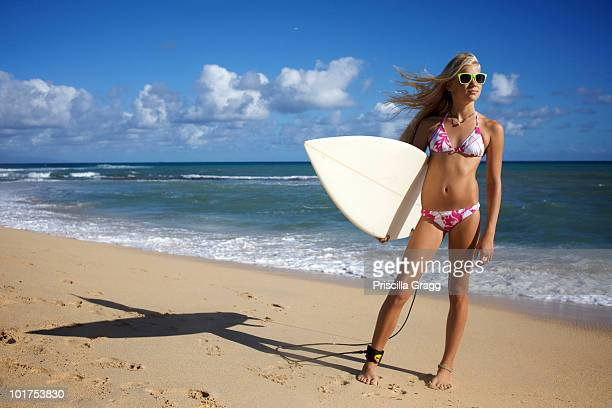 A pre-teen surfer girl wearing sunglasses poses for the camera on an early morning at Paia Beach in Maui, Hawaii.