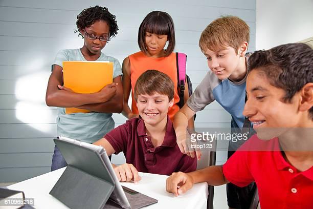 Pre-teenage friends using digital tablet, internet, social media.