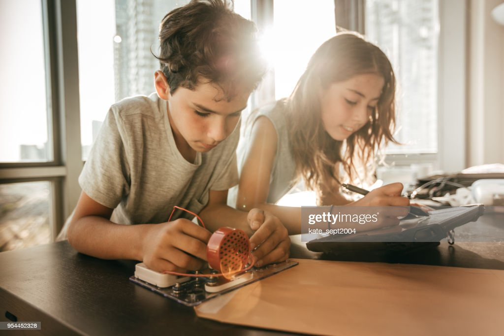 Pre-teens building new robotic system : Stock Photo