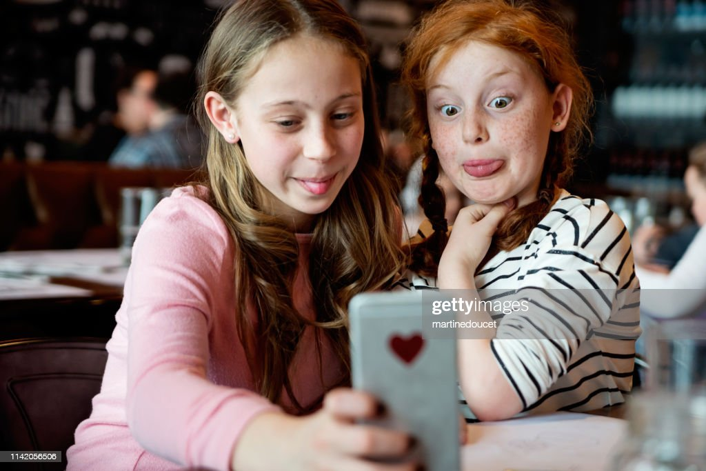 Preteens girls doing selfies at a restaurant table. : Stock Photo