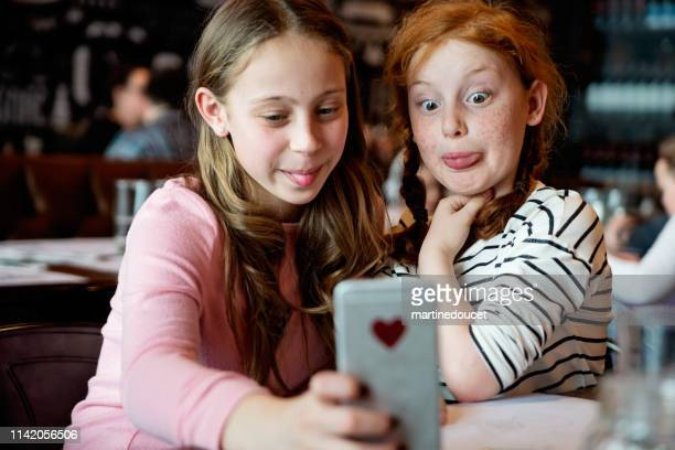 Preteens girls doing selfies at a restaurant table.