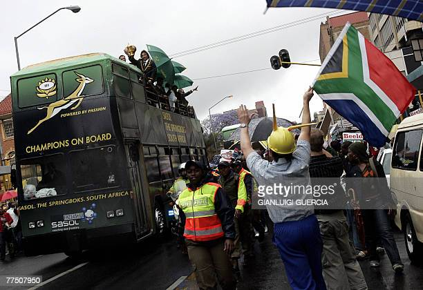 Pretoria residents celebrate under heavy rain, 26 October 2007, the South African rugby union national team during a public parade in the streets of...