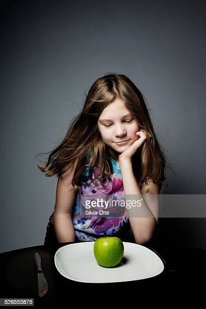 Pretty 12 year old girl looking at plate with appl