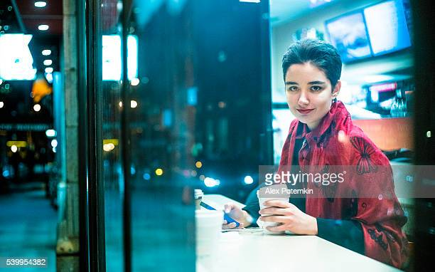 Pretty 19-years-old girl using smartphone in cafe