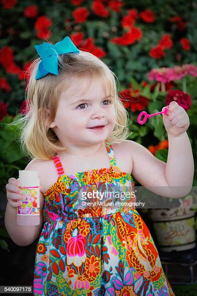 Pretty 2-year-old in colorful dress with bubbles