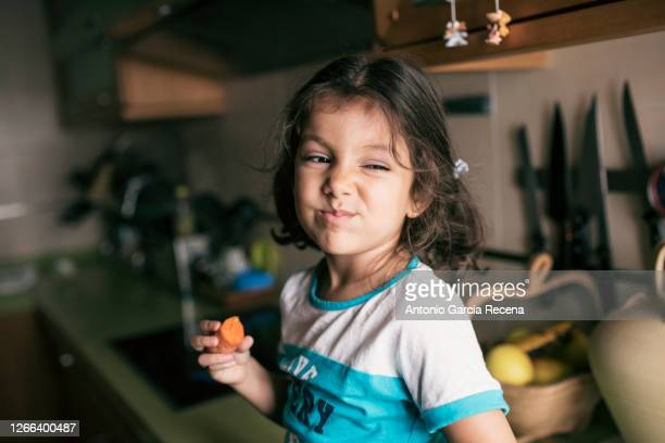 pretty 4 years girl eating carrot in kitchen, sitting on her kitchen counter - 4 5 years stock pictures, royalty-free photos & images