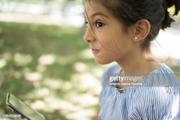 pretty 7 years old girl in park looking phone - 6 7 years stock pictures, royalty-free photos & images