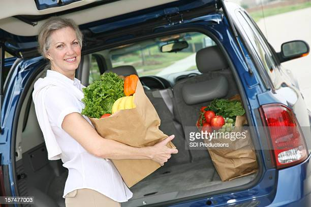 Pretty Adult Woman Holding Groceries at Car