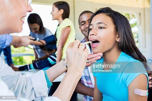 pretty african american girl getting health examination - throat photos stock photos and pictures