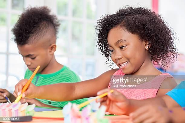 Pretty African American little girl in art class