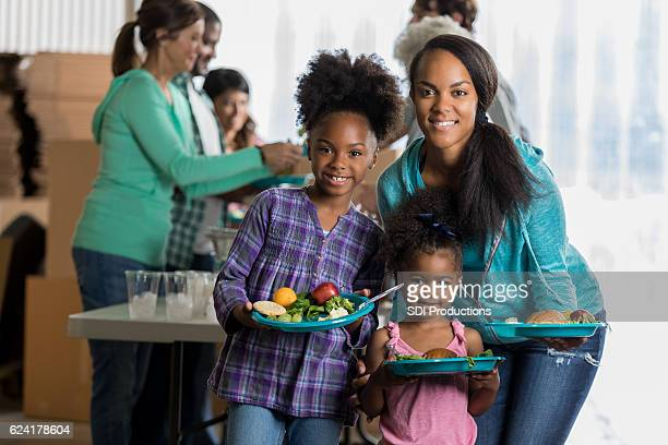 Pretty African American mom and daughters at soup kitchen