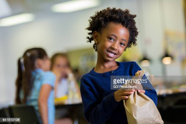 pretty african american school girl in school cafeteria - lunch bag stock pictures, royalty-free photos & images