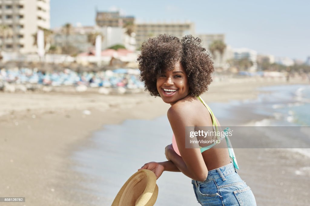 pretty afro american girl holding hat on beach laughing stock photo