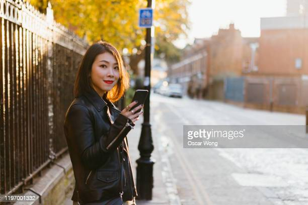 pretty and smiling young woman looking at camera while using mobile phone on the street in europe - looking at camera stock pictures, royalty-free photos & images