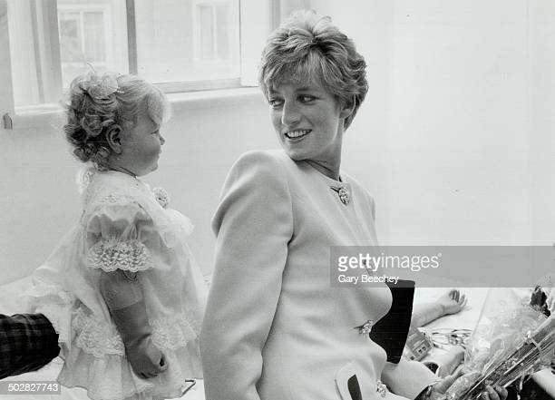 Pretty as a princess Brittany Kwacz a big 1 1/2 years old and with an artificial arm has a shy smile for Diana Princess of Wales at the Hugh...