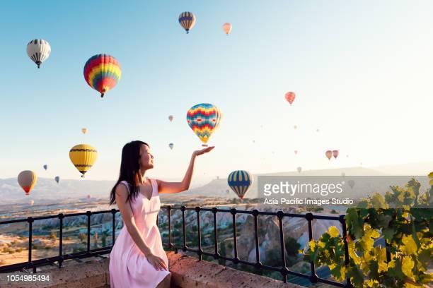 カッパドキア、トルコで谷の上を飛んでカラフルな熱気球を見てかなりアジアの少女オープンアームズ - アナトリア ストックフォトと画像