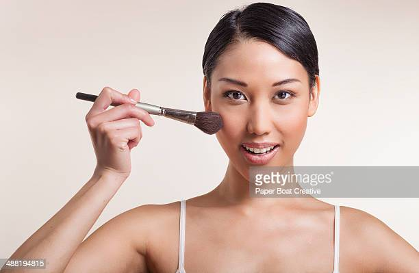 Pretty Asian woman brushing blush on her cheek