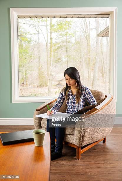 Asiático Bonita mujer Dibujar del hogar.