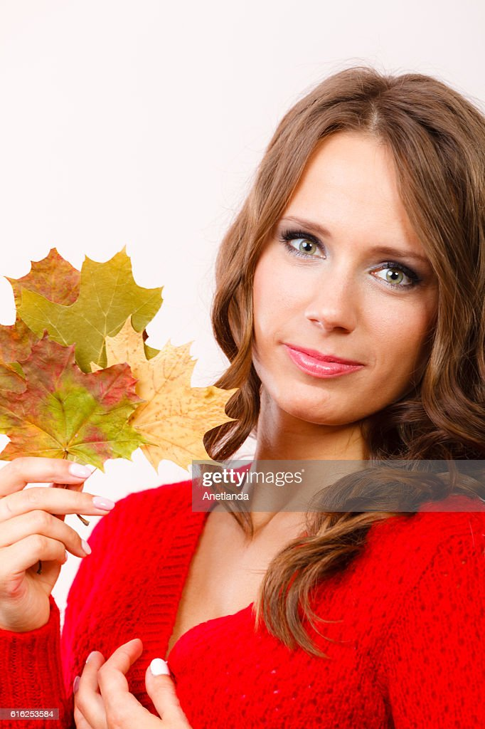 Pretty autumnal girl with maple leaves in hand : Stock Photo