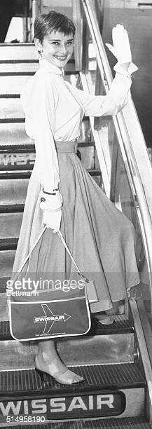 Pretty award winning stage and screen actress Audrey Hepburn waves goodbye to New York as she boards a Swissair plane at Idlewild Airport for a...