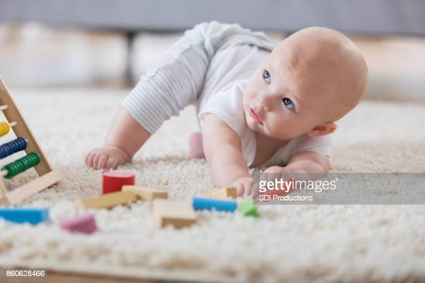 Pretty baby girl reaches for toy block