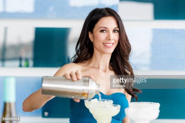Pretty bartender making margaritas