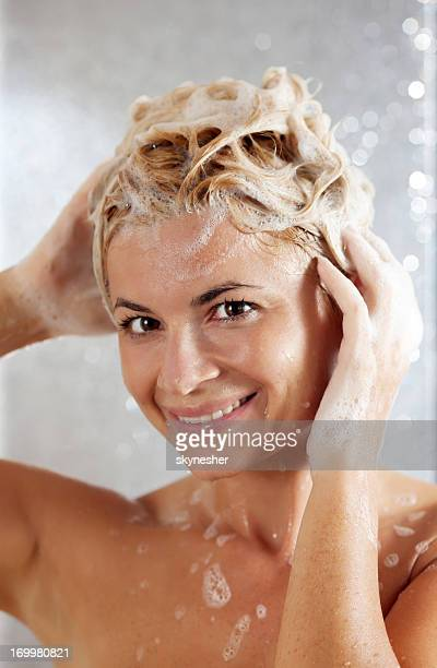 Pretty beautiful woman washing her hair in a shower.