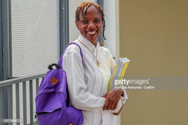 a pretty black female african student carrying books and a school bag and smiling - nairobi stock pictures, royalty-free photos & images