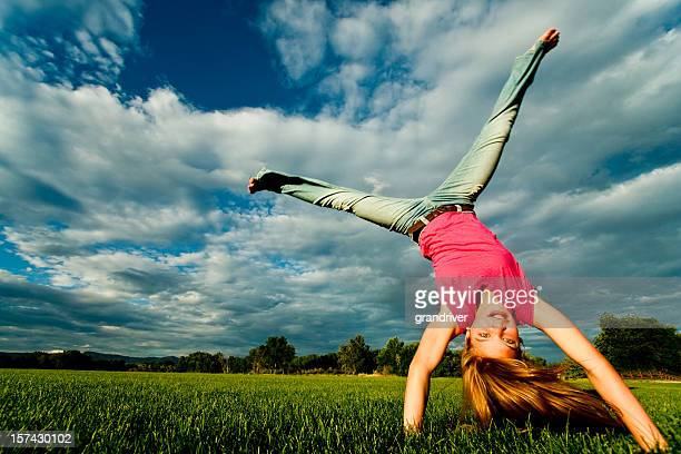 pretty blond caucasian girl doing a cartwheel - cartwheel stock pictures, royalty-free photos & images