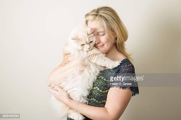 A pretty blond woman hugging a pretty blond cat