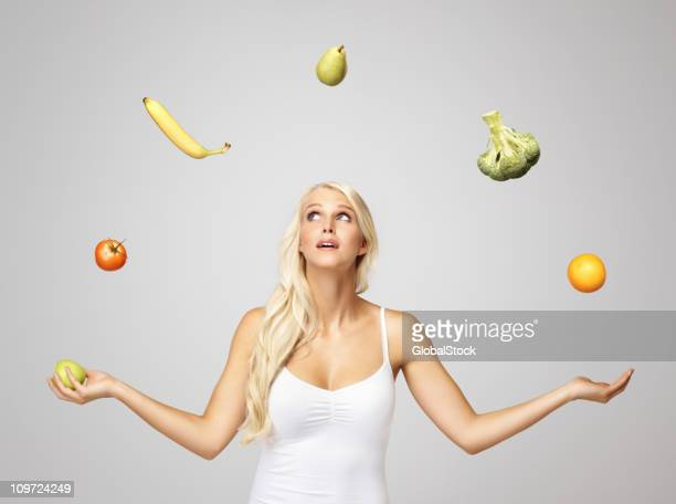 Pretty blond woman juggling fruits
