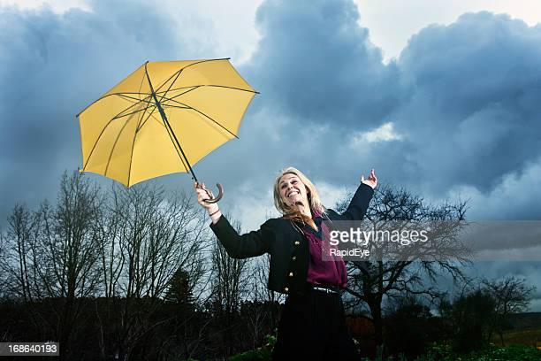 Jolie blonde danse heureux avec parapluie dans un orage jaune