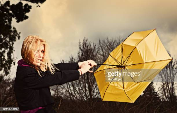 Pretty blonde desperately wrestling with umbrella in storm