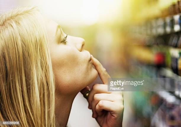 Ziemlich Blond, finger auf den Lippen, choosng Produkt von Supermarkt-Regal