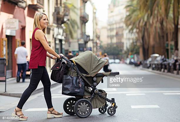 Pretty blonde mother walking in southern european city with pushchair
