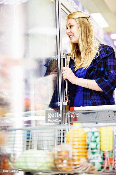 Pretty blonde reaching into vertical fridge in supermarket, smiling