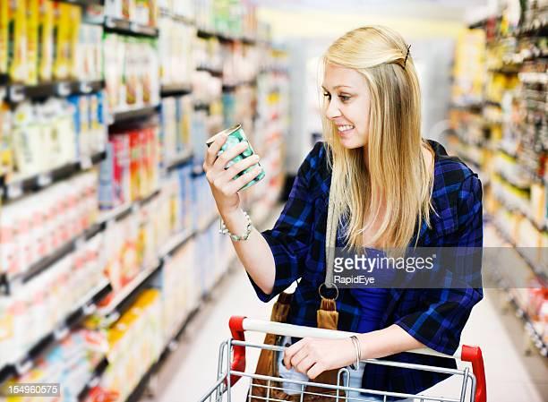 Pretty blonde shopper choosing canned peas in supermarket